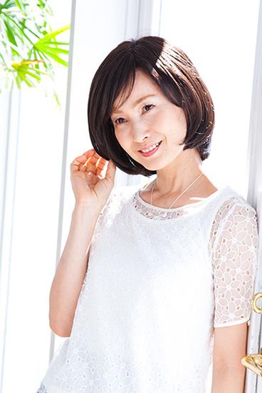 ミディアムスタイルのウィッグを着用した女性が陽当たりの良い窓際で誰かと話しているイメージ