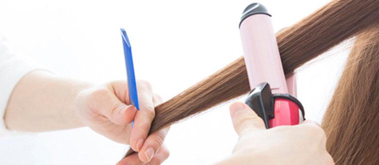 髪にアイロンを当てている美容師の手元
