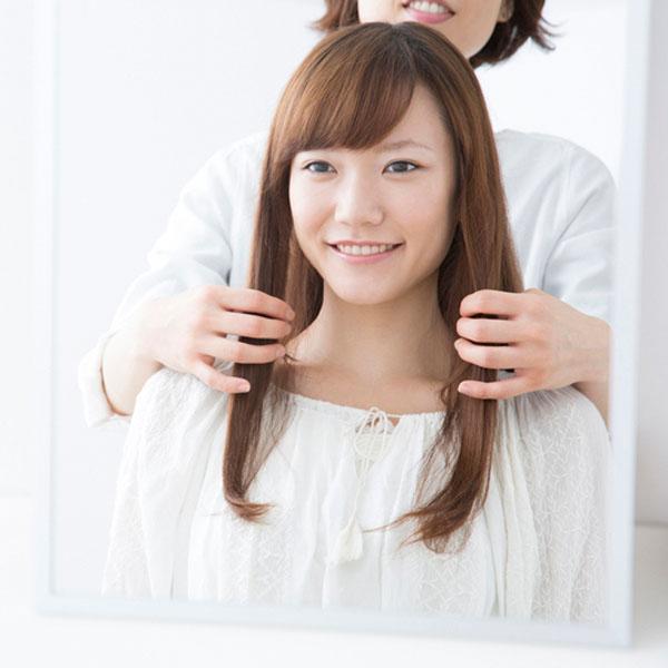 美容室で鏡を見ながら美容師と話している女性のイメージ