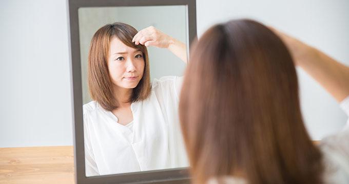 鏡を見て前髪を気にしている女性