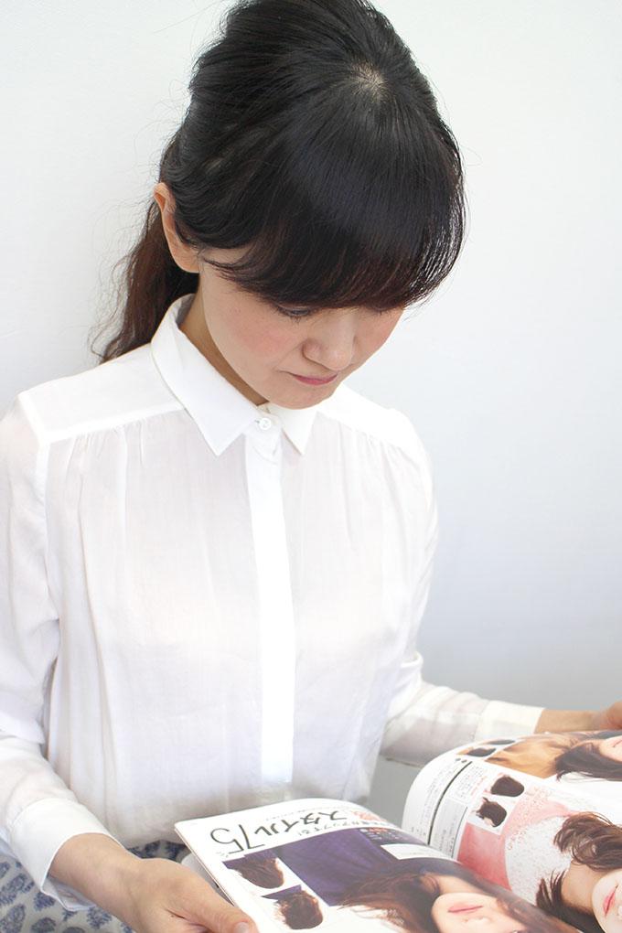 ヘアカタログで髪型を選んでいる女性の写真
